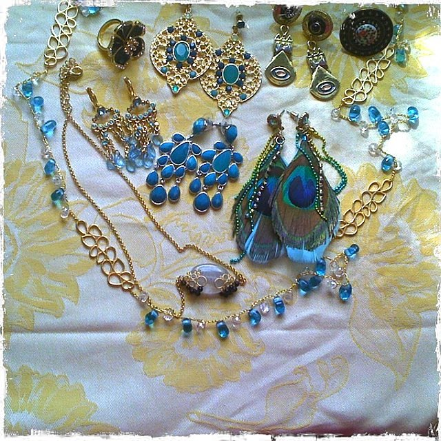 "Gold and blue necklace from Send the Trend; black and gold necklace with white quartz stone from Bauble Bar; Blue and gold earrings from college; black and gold flower ring from Bauble Bar; teal blue stone cascade earrings from Bauble Bar; gold plated and teal jeweled teardrop earrings from Send the Trend; black and gold ""World's End"" earrings from Jewelmint; round filigree ring from Charming Charlie; peacock feather earrings from Forever 21."